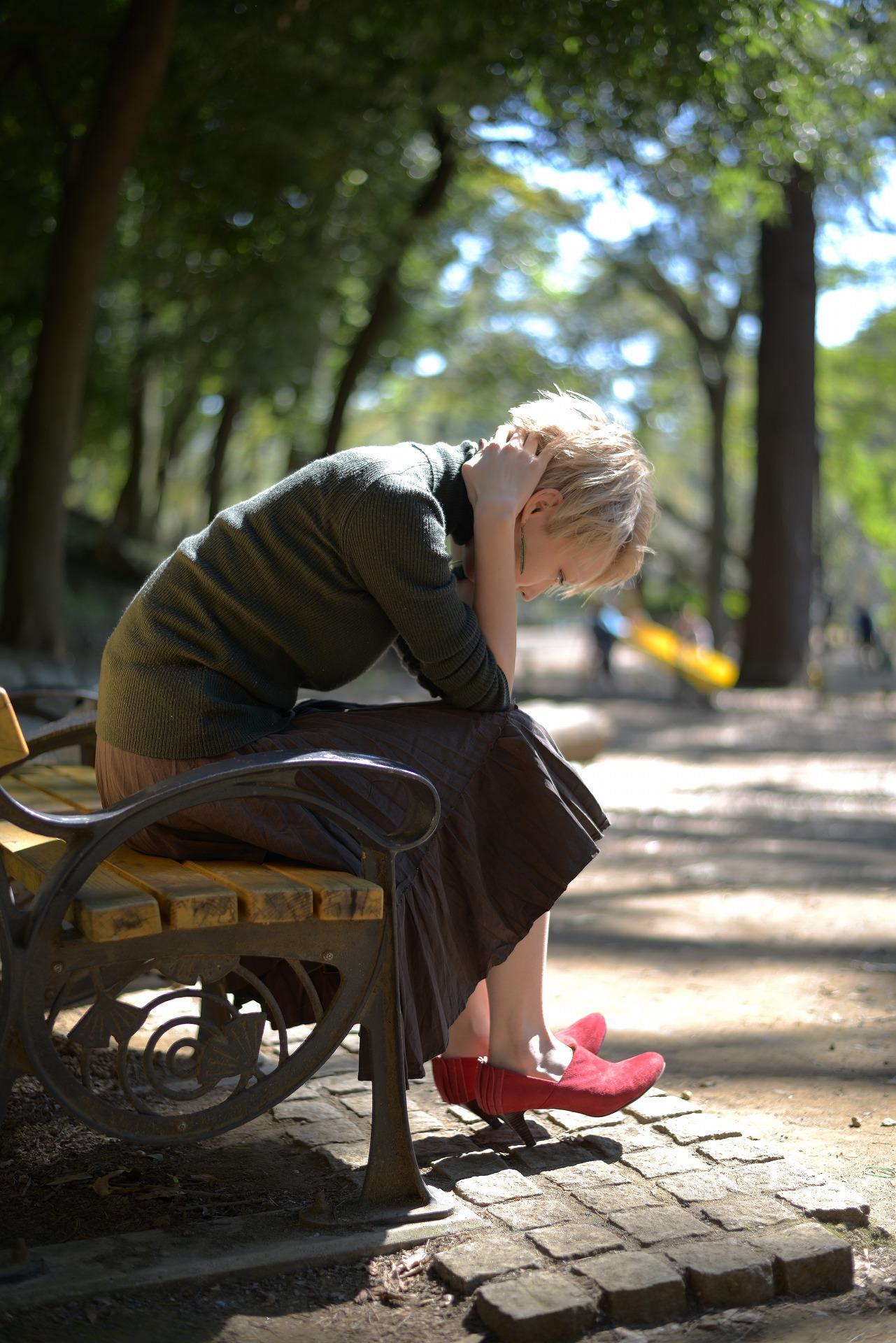 公園のベンチで「どうしたらいいの」と落ち込む女性