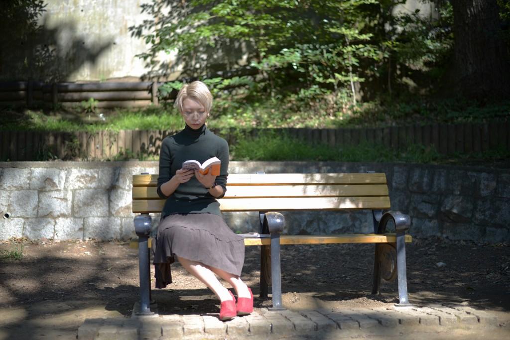 公園のベンチで読書に没頭するインテリ女子
