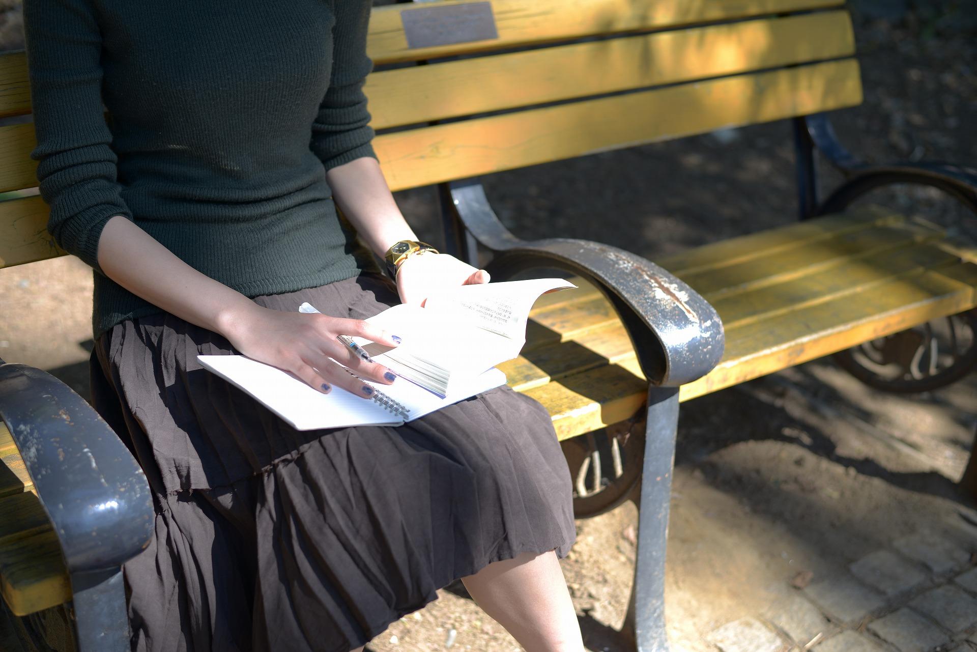 公園のベンチで本を読みながら勉強する