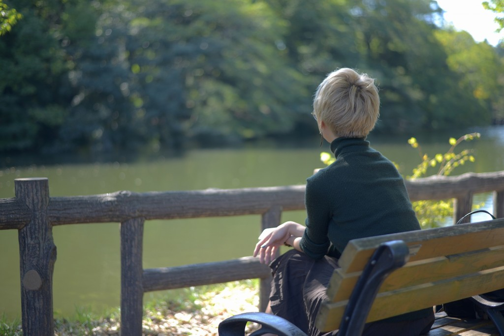 公園のベンチから湖を見て思いふけっている