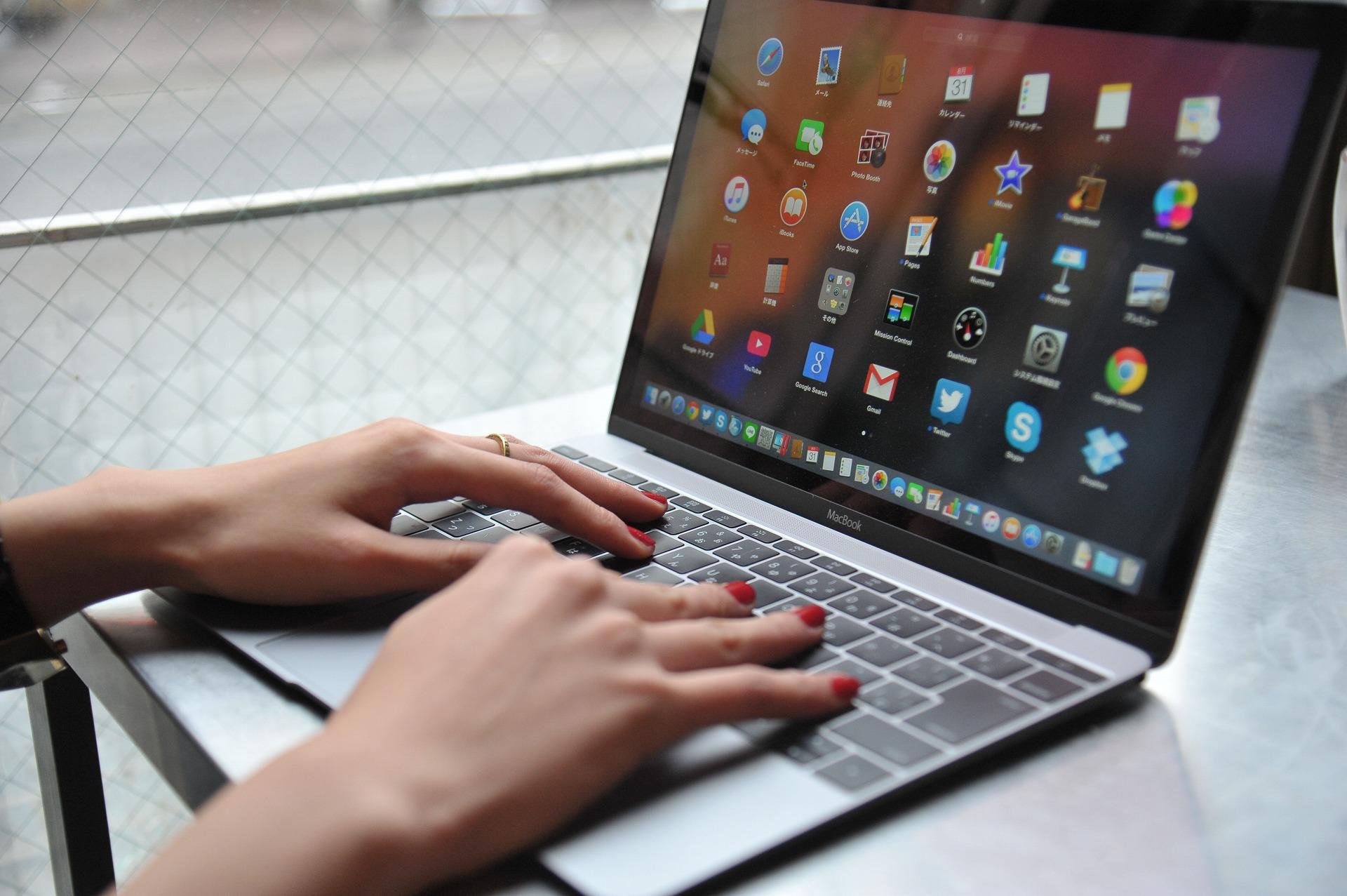 ノートパソコンで作業する赤いマニキュアの手