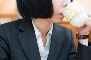 ファミレスのコーヒーで一息つくキャリアウーマン
