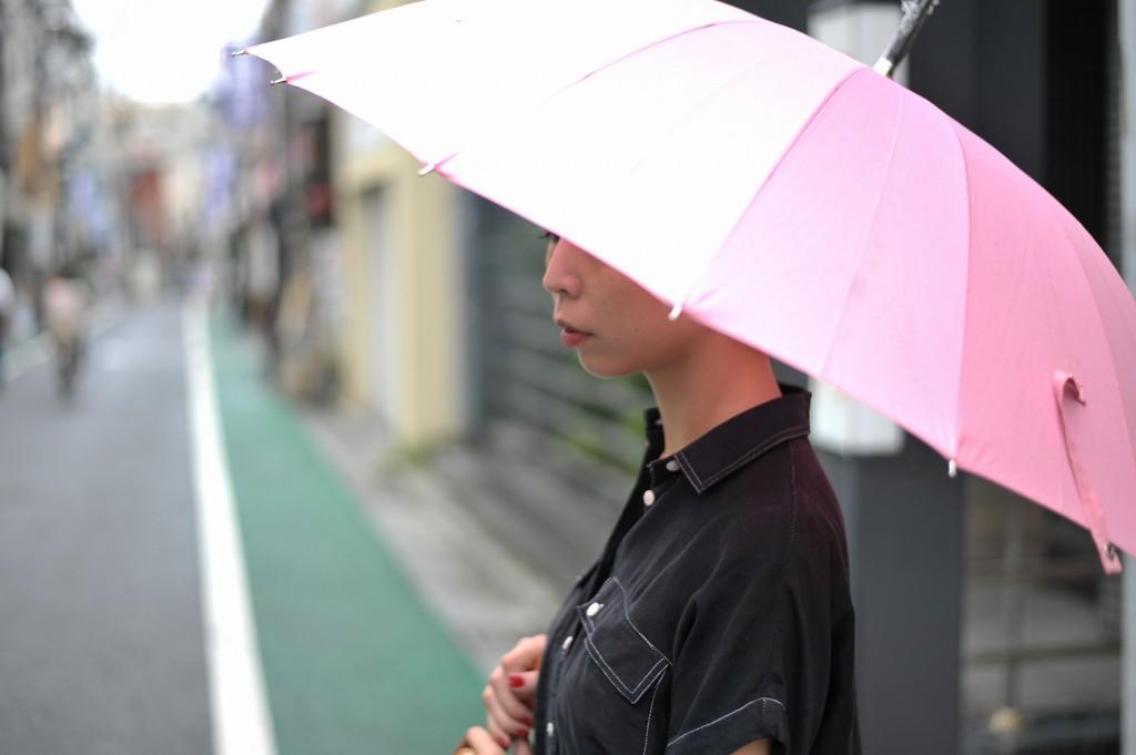 ピンク色の傘をさして雨をしのぐ