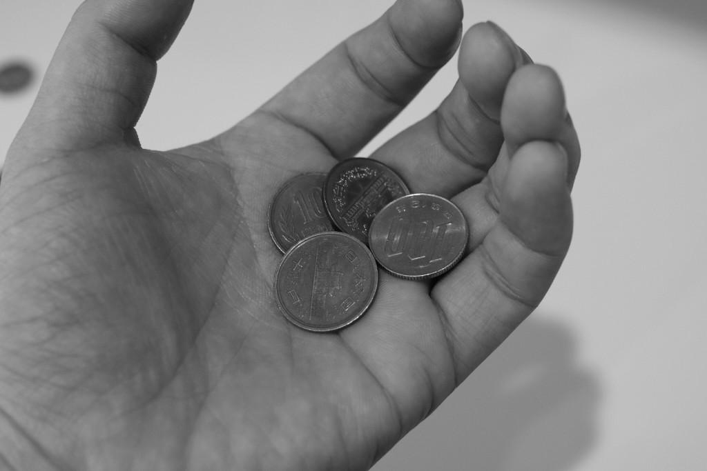 株価の暴落により小銭を手のひらで抱きしめる