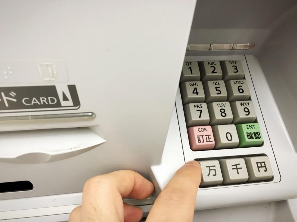 いくらお金を下ろすかボタンの手前で戸惑う指