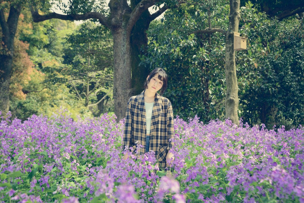紫色のスミレの花畑に囲まれる