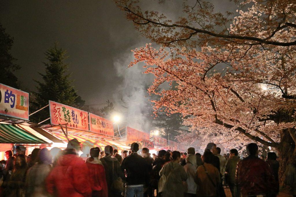 夜桜のライトアップと賑やかな屋台