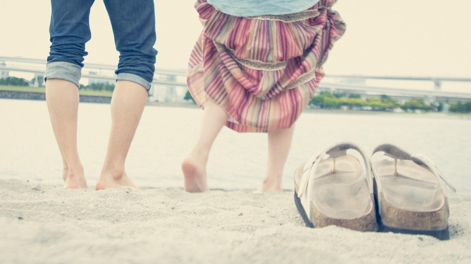 浜辺で裸足になる男女2人
