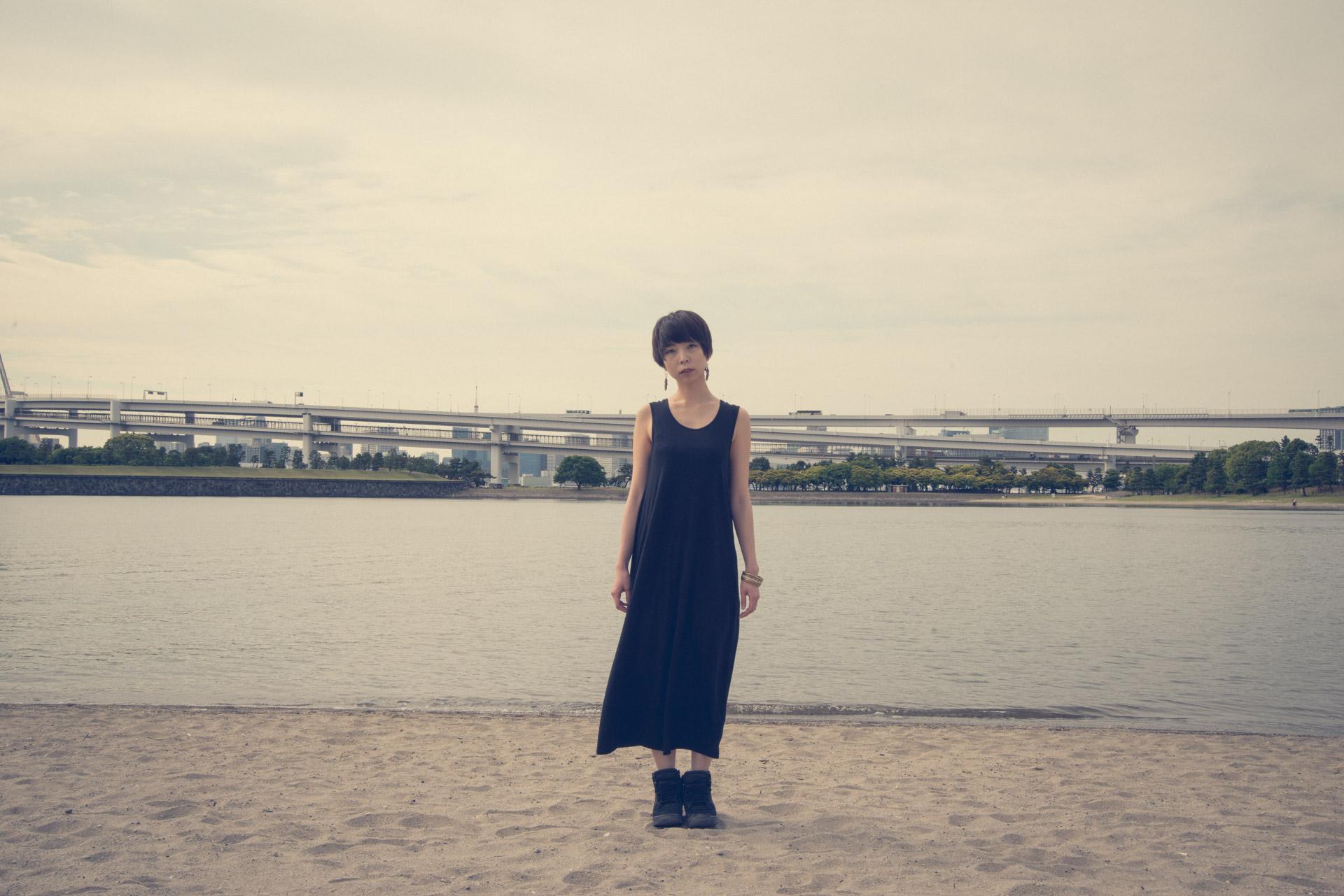 海をバックに砂浜に立ちすくむワンピースの女性