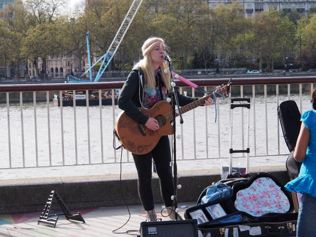 ロンドンのテムズ川で歌うストリートミュージシャン