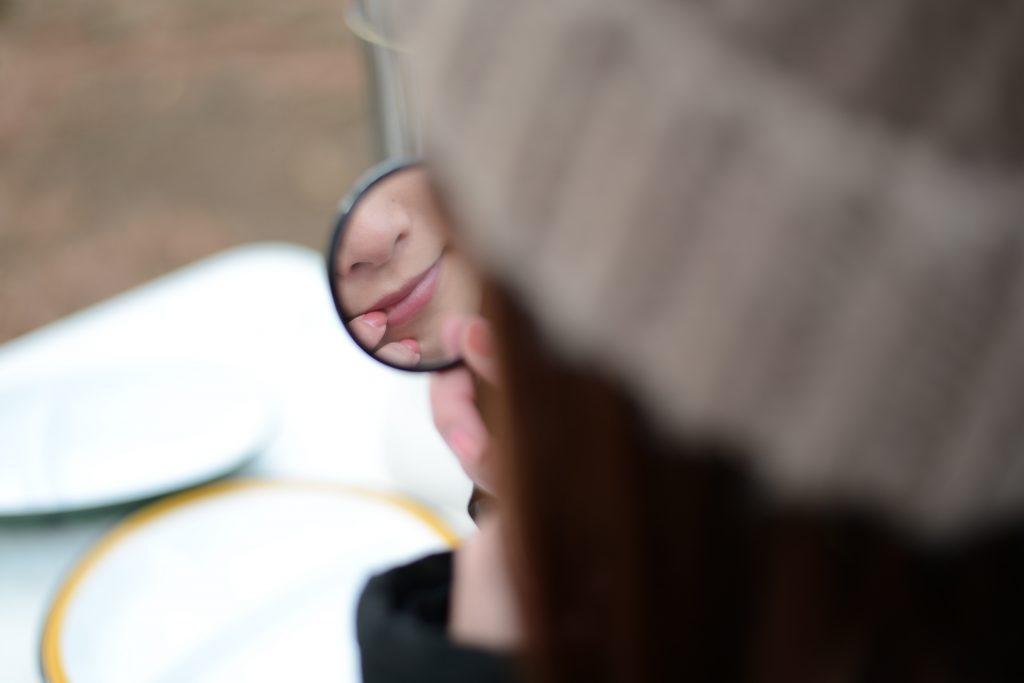 冬の公園で唇が乾燥してないか鏡でチェック