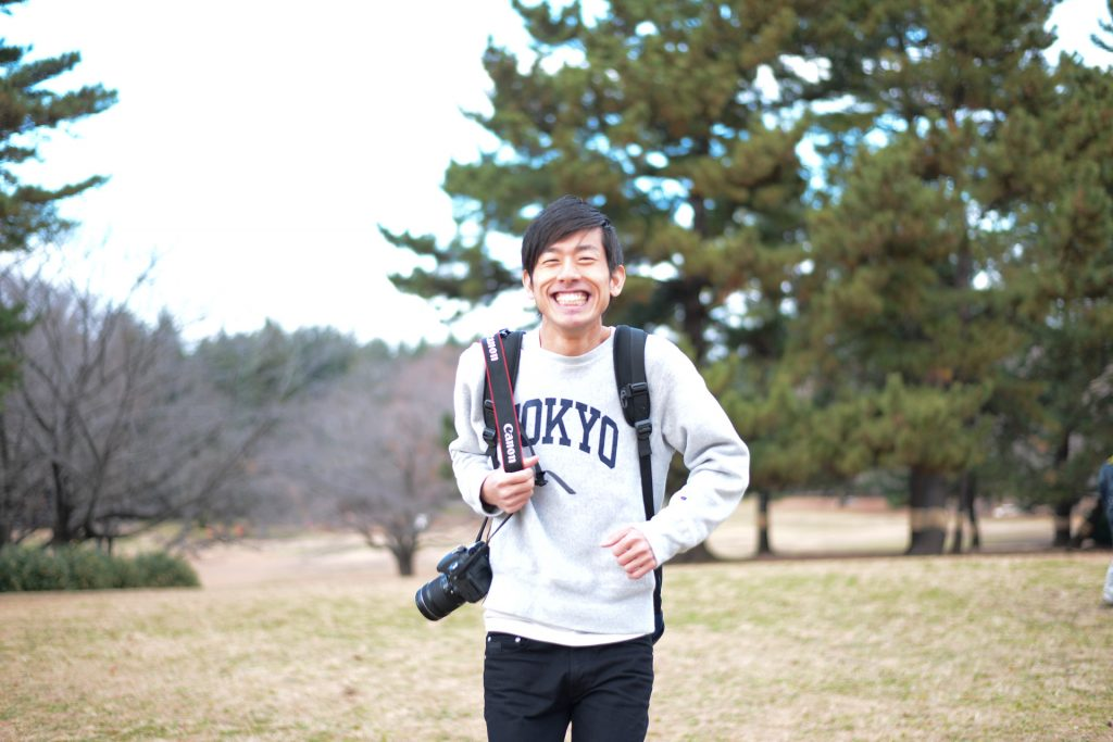 爽やかな笑顔の駆け出しカメラマン