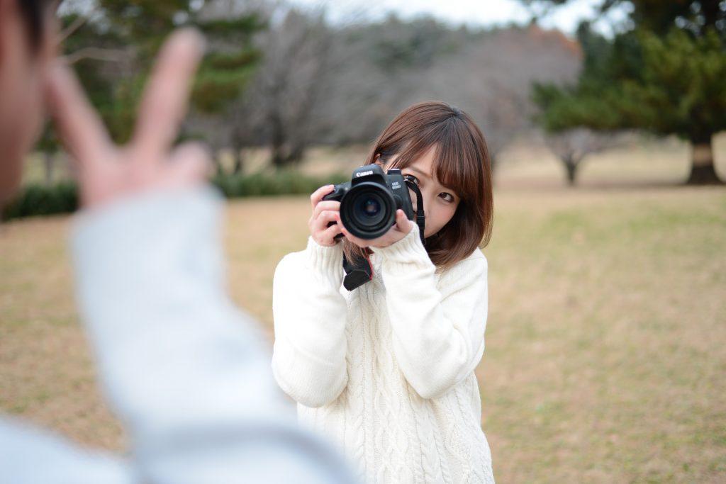 不慣れな手つきで被写体を撮影するカメラ女子