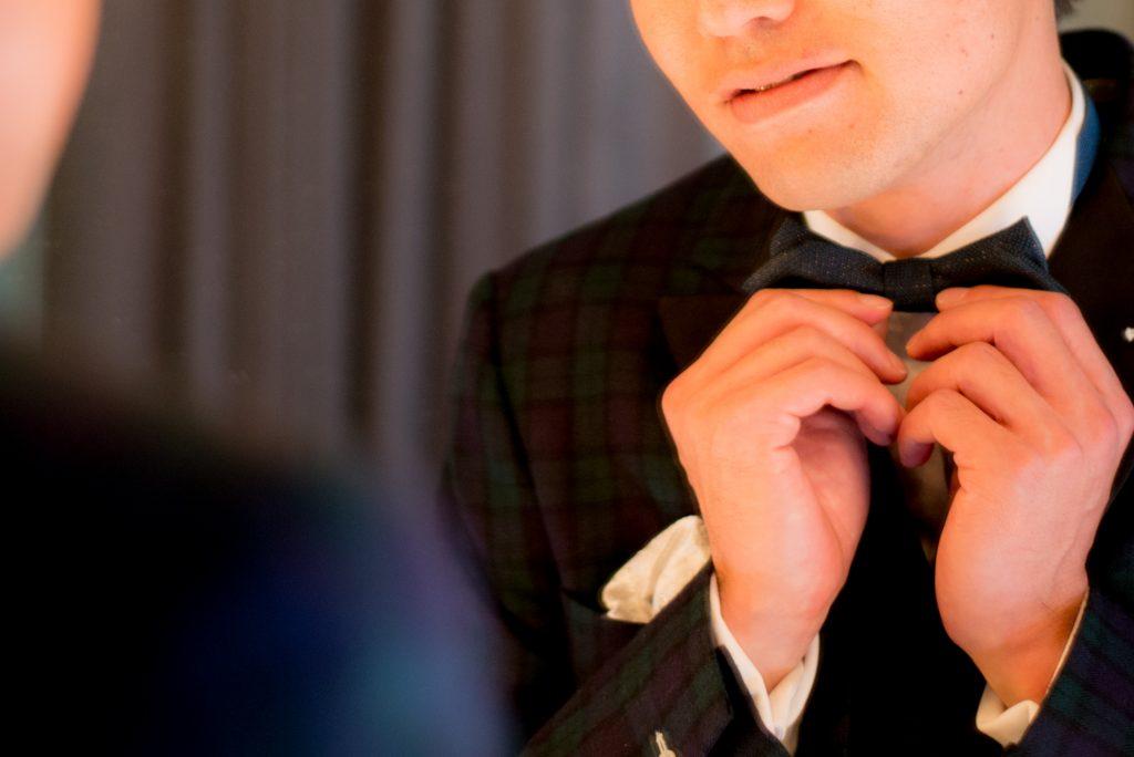 蝶ネクタイを整える新郎