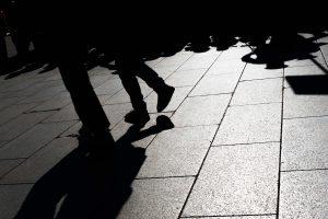 街を歩き朝日を浴びる人々の影