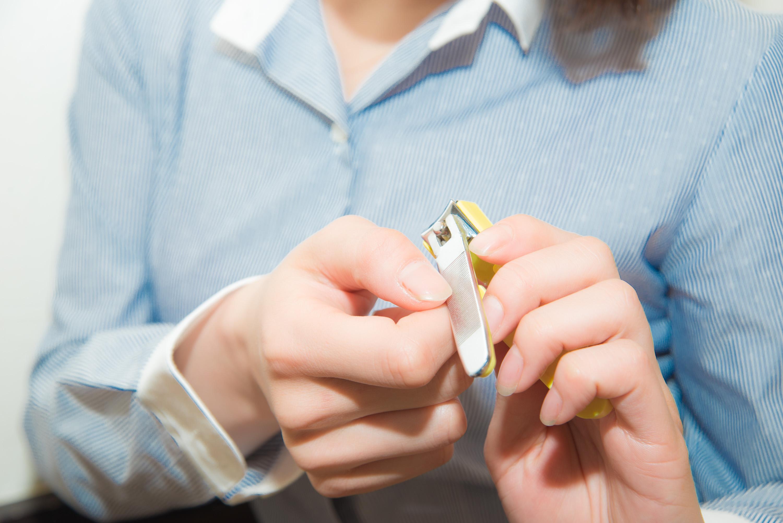 爪切りで爪を研ぐ女性