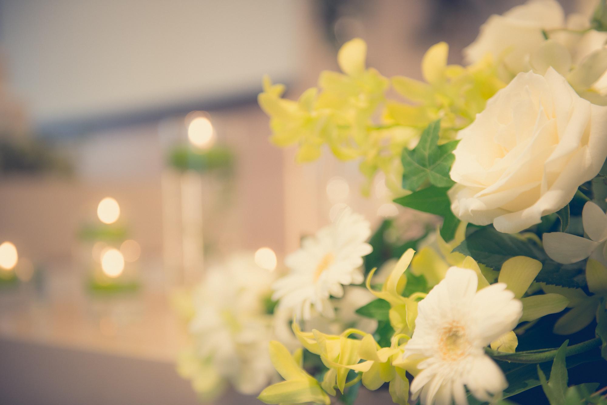 教会を照らすキャンドルと白い薔薇