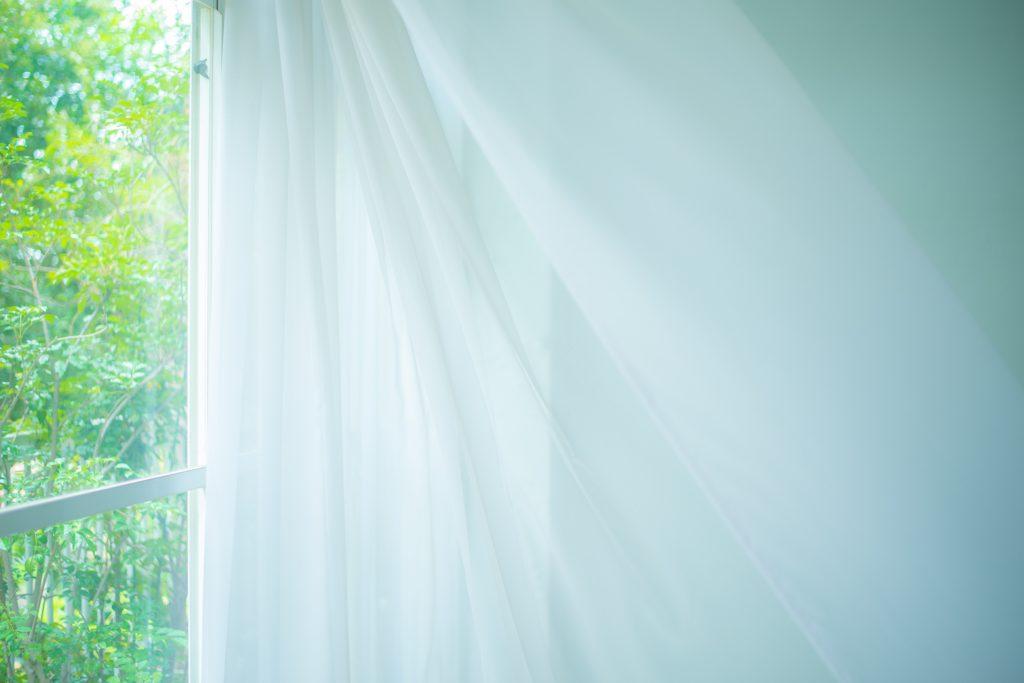 そよ風を感じる緑に囲まれた白いカーテン