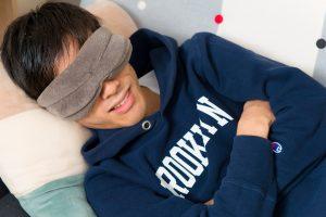 アイマスクをしてソファで眠る
