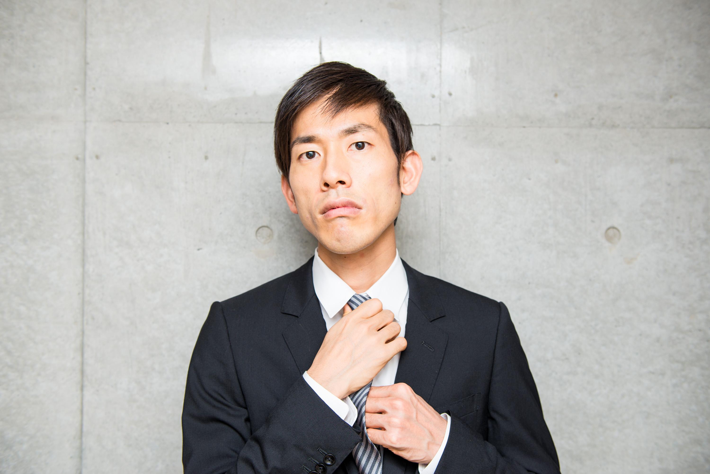 ネクタイの角度を調整するサラリーマン