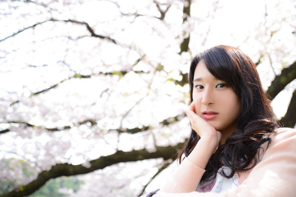 桜と桜色のカーディガンを着た花見ガール