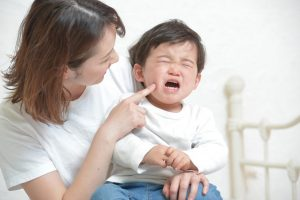 泣き出した子供をあやすお母さん