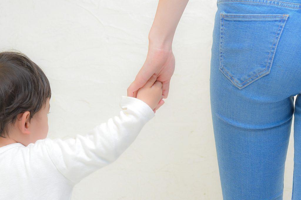 お母さんの手を離さない男児