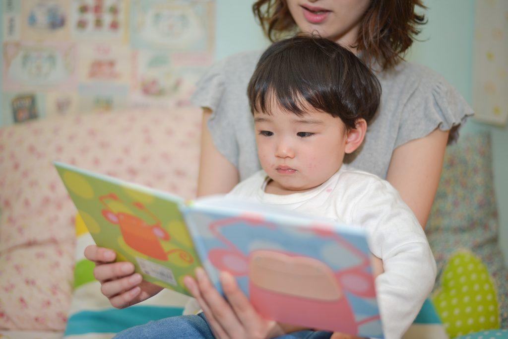 絵本を読み聞かせるお母さんと夢中な子供