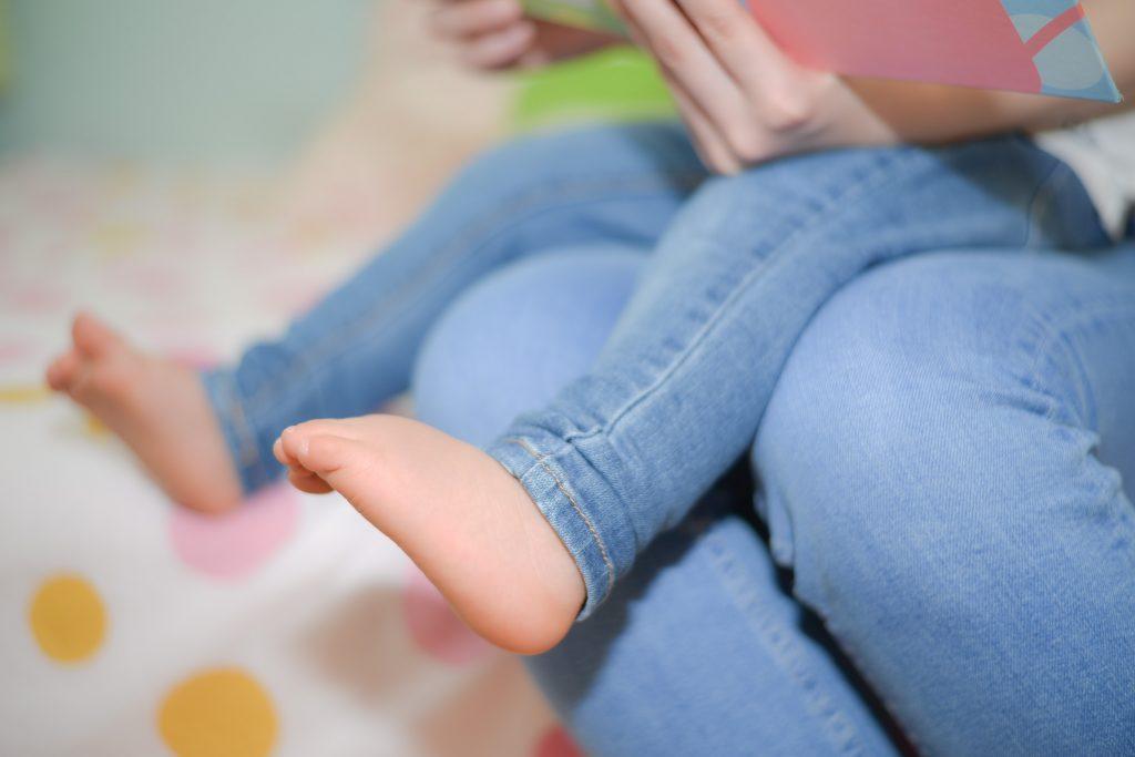 お母さんの膝の上に座る子供の足